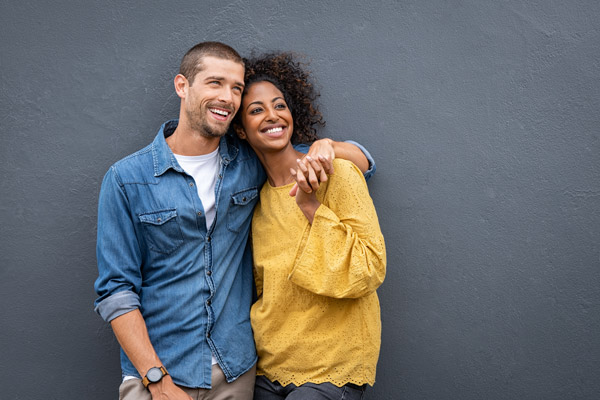 diverse-couple-laughing-holding-hands
